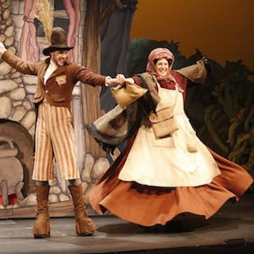 Two people on stage dressed in old-timey peasant clothing with their arms outstretched and holding hands in the middle.