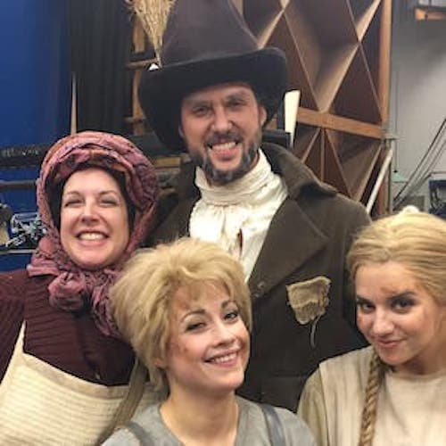 Four people in period costumes facing a camera and smiling for a candid shot in the dressing room.