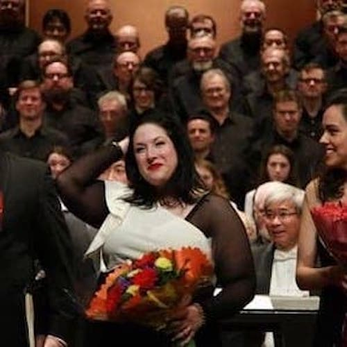 Three people standing on stage in front of a chorus. They are each holding huge bouquet in their arms.