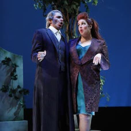 a man in a suit and a woman wearing a blue dress and purple blazer mid-song on stage.