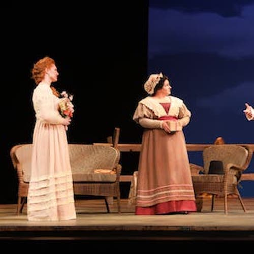 A scene on stage where 4 poorly-dressed people are standing across from someone in uniform.