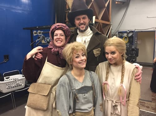 four people in costume smiling at the camera backstage. They are dressed like old-timey German peasants.