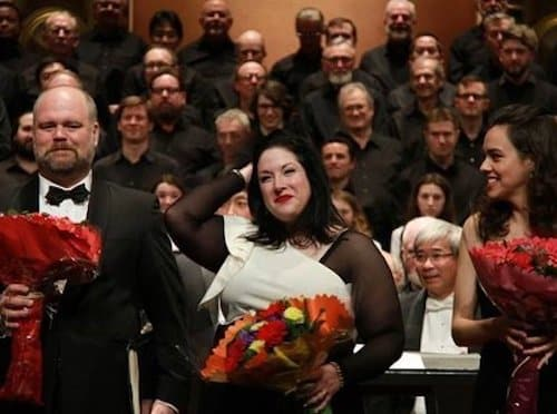 Three people standing in front of a choir on stage. Leah is in the center and all three are holding bouquets of red flowers.